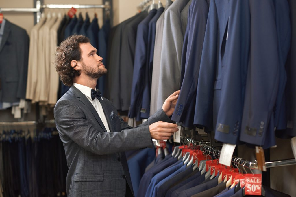 Young handsome man in costume looking for jacket in shop
